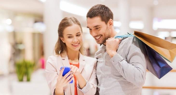 Couple looking at mobile phone while shopping